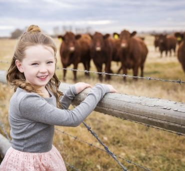 Girl hanging with some cows