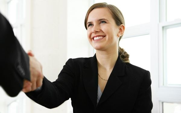 Woman in Black Suit Shaking Someones Hand