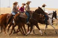 Group of cowgirls riding their horses